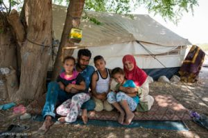 "A Syrian refugee family in the Jordan Valley, Jordan, where they have lived in a tent for four years. From left to right Na'ama, 8, Hussein, 31, Khalif, 10, Farah, 6, and their mother Asia 27. The family fled their home in Hama when the war reached their community.  ""We saw people getting shot, and we lost cousins and uncles.  That's why we left,"" said Asia, 27. It took the family two days to reach jordan. ""It was dangerous. When we reachd the border we walked for an hour.  We were scared,"" said Asia, who still has a brother in Hama who she speaks with by phone when the connection allows. The family were farmers in Syria and are now making a small living from doing field work in Jordan.  But life here is hard. The tent gets incredibly hot with punishing high temperatures in summer and freezing cold and wet during the winter months. ""We do it all. From putting pipes in the ground to picking tomatores,""she said. With both working, the family makes about 12 JD  a day (about $18 a day), which is not enough to cover the 60 JD a month per child in school transportation costs for their children along with covering other needs. With the support of UNICEF through the EU Regional Trust Fund in Response to the Syrian Crisis, the three children are now attending a nearby Makani learning centre along with vulnerable Jordanian children from the host community.  The children come here every day, except Friday, to learn to read, write, do math and better integrate the children into the community. ""Jordan is good, but we always long for home,"" said Asia.  ""Everyone loves their country.  The best thing about Syria before the war was the safety. We had a really good life there.  We had a house. But now there is nothing left.  Everything we had is gone."""