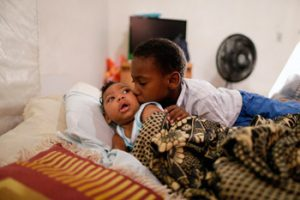 """Danilo, from Pernambuco, Brazil, is being hugged by his brother. Danilo, who has microcephaly, visits the hospital twice a week. His mother, Ana Paula, says """"With all this family love, it is easier to take care of him."""" Photo: Ueslei Marcelino/UNICEF"""