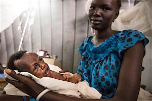 Nyankena holds her baby Both Tebg, a 2-month-old child with severe acute malnutrition, at a clinic run by UNICEF partners in Juba, the capital of South Sudan. ©UNICEF/UN053453/Gonzalez Farran
